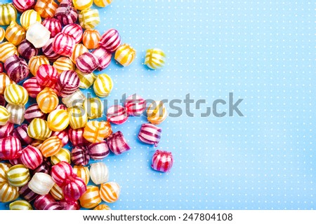 various child candies lying on blue background with polka dots and with copy space - stock photo