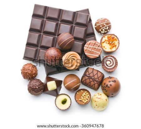 various chocolate pralines and chocolate bar on white background - stock photo