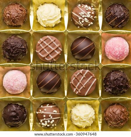 various chocolate pralines in golden box - stock photo