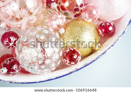 Various Christmas balls on a glitter container against a blue background. - stock photo