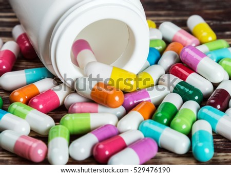 various colored pills and a vial of medication on a wooden table