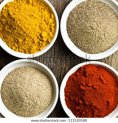 various colored spices in ceramic bowls - stock photo