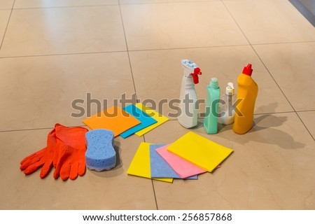Various colorful household cleaning supplies displayed on a floor with rubber gloves, clothes, a sponge and spray bottles and containers, with copyspace - stock photo
