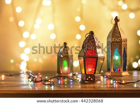 Various colorful Ramadan lamps lit up against illuminated decorative lighting background. - stock photo