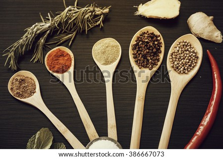 Various colorful spices on kitchen spoons