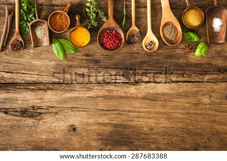 Various colorful spices on wooden table - stock photo