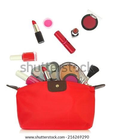 Various cosmetics coming out of a red bag isolated on white - stock photo
