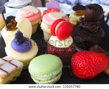 various cupcakes and macaroons with icing  and fruit - stock photo