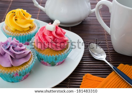 various cupcakes on a plate with tea set - stock photo