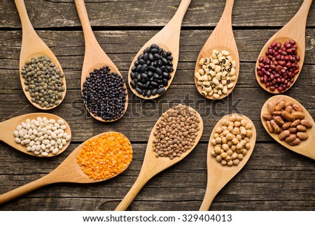 various dried legumes in wooden spoons on old table