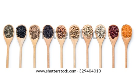 various dried legumes in wooden spoons on white background