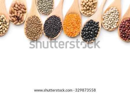 various dried legumes in wooden spoons on white background - stock photo