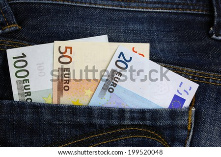 Various Euro banknotes in blue jeans pocket - stock photo