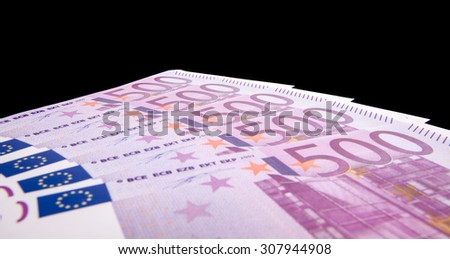 Various 500 euro notes isolated on black background - stock photo