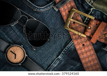 Various fashions of sunglasses, wrist watches and belt in jeans background - stock photo