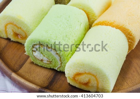 Various flavors of jam rolls on wooden dish
