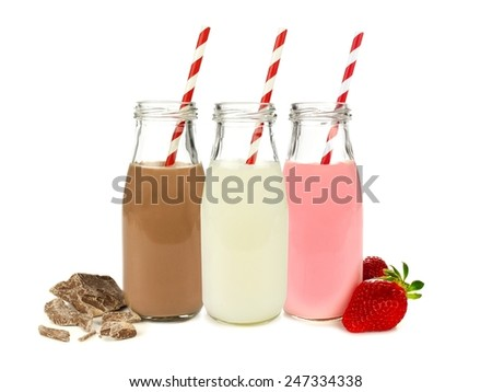 Various flavors of milk in bottles with chocolate and strawberries isolated on white                           - stock photo