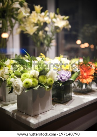 Various flower arrangements set on a white painted wooden table. - stock photo