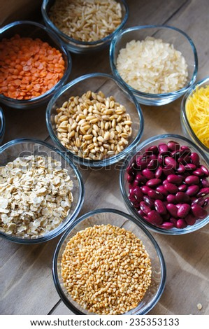 various food ingredients : beans, legumes, peas, lentils in wooden spoon and glass bowls