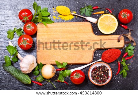 various food ingredients for cooking with empty board on dark board - stock photo