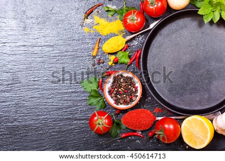 various food ingredients for cooking with empty pan on dark board