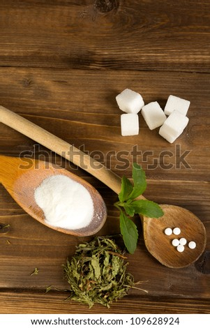 Various forms of stevia natural sweetener plus real sugar lumps on a wooden table - stock photo