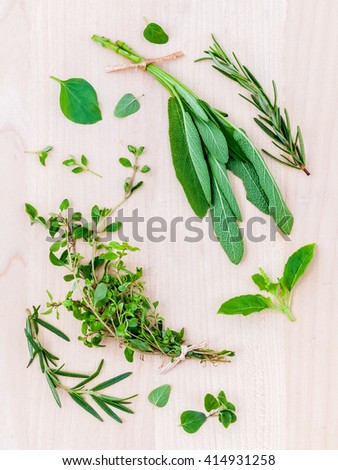 Various fresh herbs from the garden holy basil , basil ,rosemary,oregano, sage and thyme over rustic wooden background.