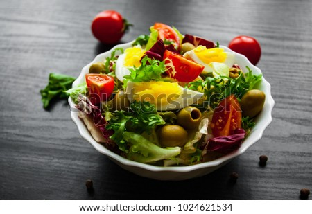 various fresh mix salad leaves with tomato, eggs and olive in bowl on dark wooden background