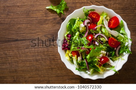 various fresh mix salad leaves with tomato in bowl on wooden background. with copy space. top view