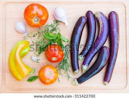 Various fresh vegetables and herbs on wooden cutting board. - stock photo
