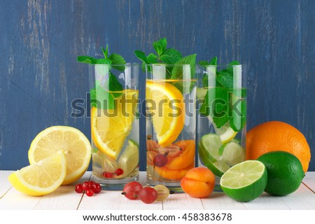 Various fresh vitamin citrus flavored fruit infused water in glasses with fruits on white wooden table against blue colored wall. - stock photo