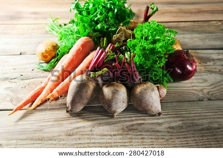 Various fresh, young homegrown vegetables, beets, carrots, parsley, dill and potatoes lies on a wooden table. rustic style - stock photo