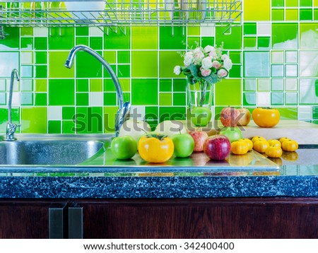 Various fruits on cabinet top in green modern kitchen/ Interior still-life - stock photo