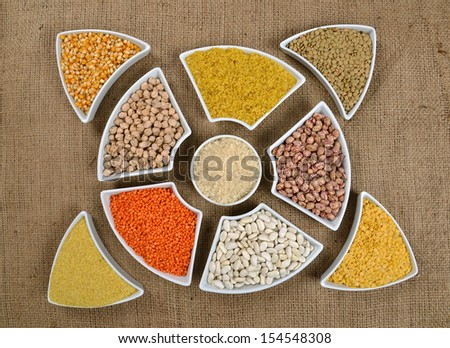 various grain, beans, legumes, peas, lentils in spoon on the sackcloth background - stock photo