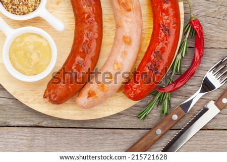 Various grilled sausages with condiments on cutting board - stock photo
