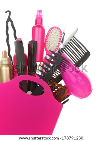 Various hairstyling equipment in shopping bag isolated on white - stock photo