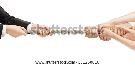 Various hands during tug war - stock photo