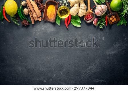 Various herbs and spices on black stone plate - stock photo