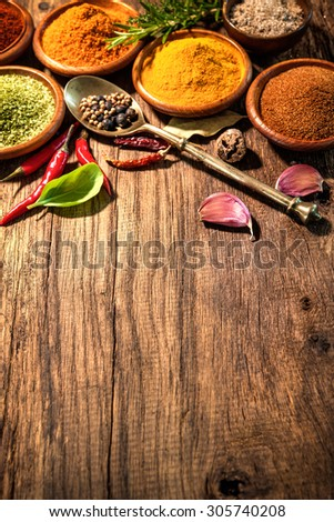 Various herbs and spices on wooden table - stock photo