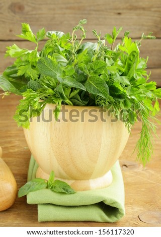 various herbs (basil, thyme, parsley, mint and dill) on wooden background