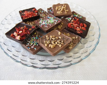 Various homemade chocolate bars on glass plate - stock photo