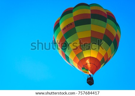 Various hot air balloons against a clear washed out blue sky.