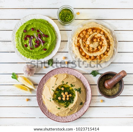 Various hummus dips. Avocado green peas hummus with pomegranate, chickpea hummus with grin olive oil and lentils hummus with paprika.