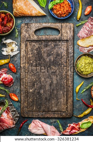 Various ingredients for bruschetta or crostini making: smoked meat, Sausage, ham ,pesto, dry tomatoes, peperoni around blank old cutting board on rustic background, top view. Italian food  concept. - stock photo