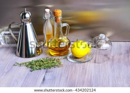 Various ingredients for salad dressing: oil, olive oil, vinegar, grape vinegar, wine vinegar, balsamic or soy sauce, fresh lemon, thyme. Oil glass and steel jug, oil bottles, kitchen glass,  - stock photo