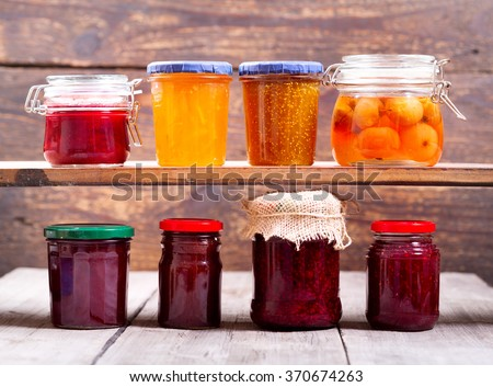 various jars of fruit jam on wooden background