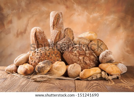 Various kind of bread on wooden surface - stock photo