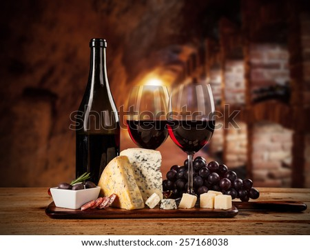 Various kind of cheese with red wine in cellar - stock photo