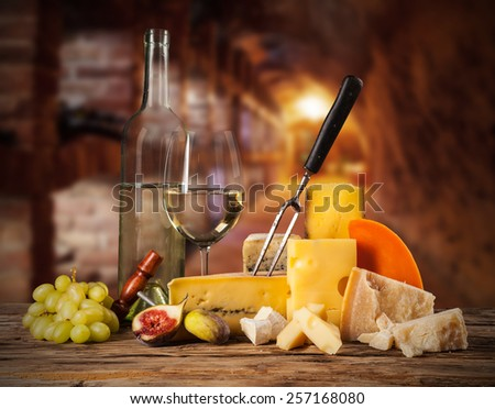 Various kind of cheese with white wine and fruit. - stock photo