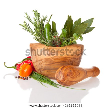 Various kind of fresh herbs in wooden grinder. Isolated on white background